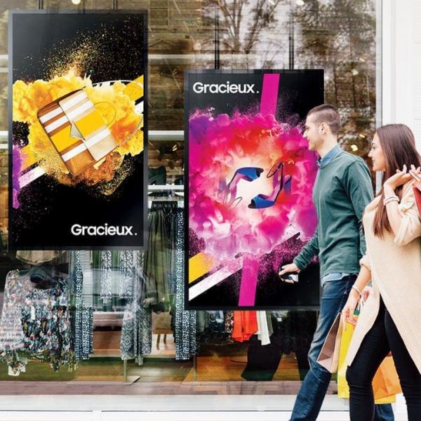 Viser to personer som går forbi et butikkvindu med digitale skilt i bakgrunnen